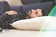 Young man at home lying on couch - FMOF00169