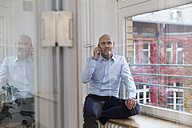 Businessman on cell phone at the window - FKF02127