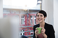 Portrait of smiling woman holding cup of coffee at the window - FKF02151