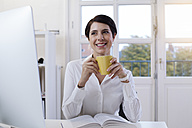 Smiling woman holding cup of coffee at desk in office - FKF02154