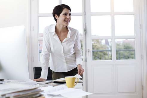 Smiling woman at desk in office - FKF02157