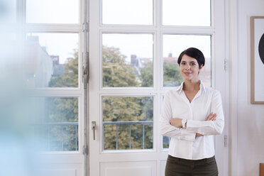 Portrait of confident woman standing at the window - FKF02160