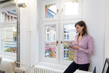 Woman using tablet at the window in office - FKF02172