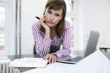 Woman with laptop in office thinking - FKF02178