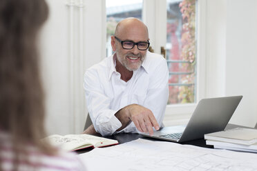Smiling businessman using laptop in office - FKF02181