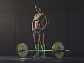 Young woman preparing to lift barbell - MADF01332