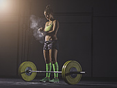 Young woman preparing to lift barbell - MADF01335