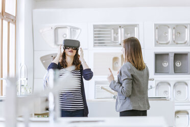 Customers consulting saleswoman in shop for kitchen sinks - ZEDF00507