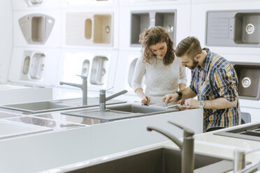 Customers consulting saleswoman in shop for kitchen sinks - ZEDF00516