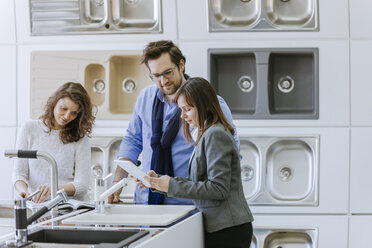 Customers consulting saleswoman in shop for kitchen sinks - ZEDF00519
