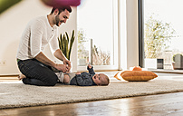 Father changing diapers and playing with his baby son - UUF09867