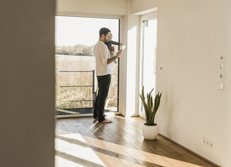 Father standing at home, carrying baby son and reading text messages - UUF09870