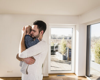 Father holding and hugging his baby son, standing in comfortable home - UUF09876