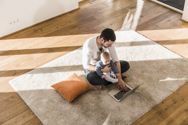 Father sitting cross-legged with baby son on lap, using laptop and smart phone - UUF09882