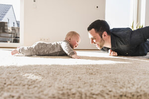 Father and baby son playing crawling on carpet - UUF09900