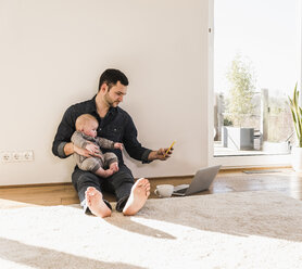 Father with baby son reading messages sitting on floor - UUF09906
