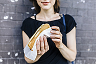 Woman's hand holding Hot Dog, close-up - GIOF01865