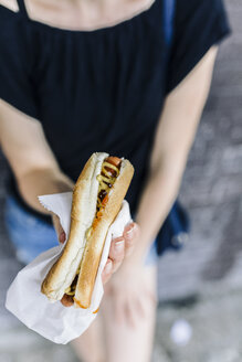 Woman's hand holding Hot Dog, close-up - GIOF01868