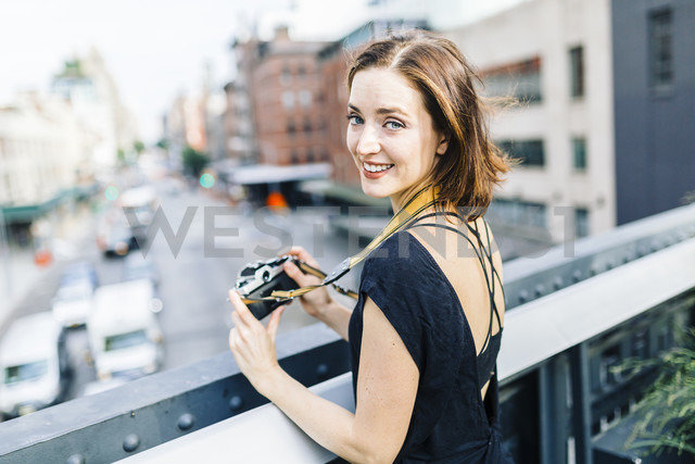 USA, New York City, smiling woman with camera on the High Line in Manhattan - GIOF01874