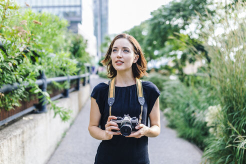 USA, New York City, woman with camera on High Line Park in Manhattan - GIOF01880