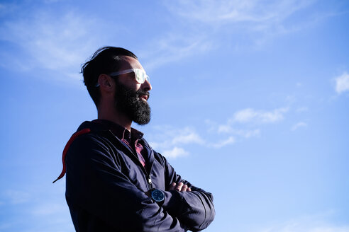 Portrait of man with full beard and sunglasses in front of sky - SIPF01405