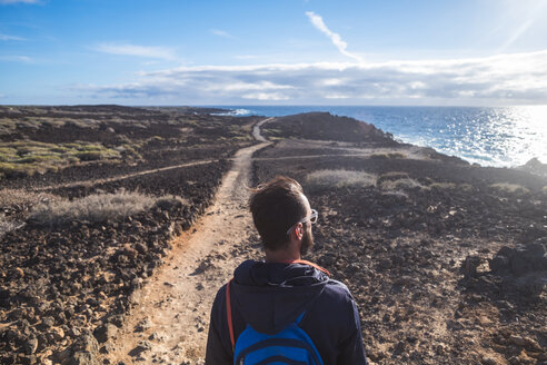 Spain, Tenerife, hiking man looking to the sea - SIPF01414