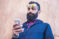 Portrait of man with full beard looking at cell phone - SIPF01420