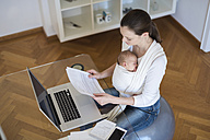 Mother with baby girl in sling working from home - DIGF01514