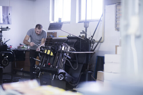 Young man working in printing shop - SGF02121