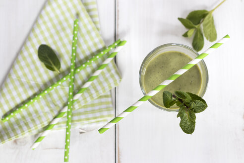 Glass of green smoothie garnished with mint leaves - YFF00646