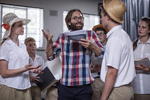 Drama teacher eading students wearing props - ZEF12813