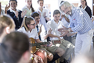 Teacher and students having music lessons outside - ZEF12816
