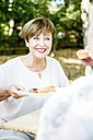 Smiling senior woman offering muffins - WESTF22683