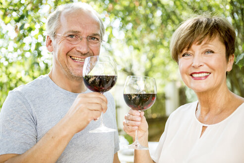 Happy senior couple having glass of red wine outdoors - WESTF22692
