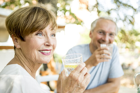 Smiling senior woman drinking glass of water with husband in background - WESTF22698