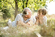 Happy senior couple lying in meadow - WESTF22716