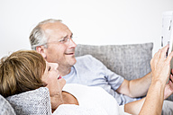 Senior couple at home lying on couch using digital tablet - WESTF22731
