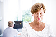 Serious senior woman with husband in background using computer - WESTF22740