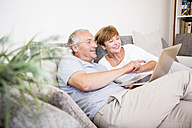 Senior couple at home sitting on couch using laptop - WESTF22746