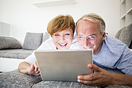 Happy senior couple at home lying on couch using digital tablet - WESTF22752