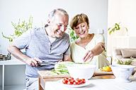 Happy senior couple in kitchen preparing salad together - WESTF22755