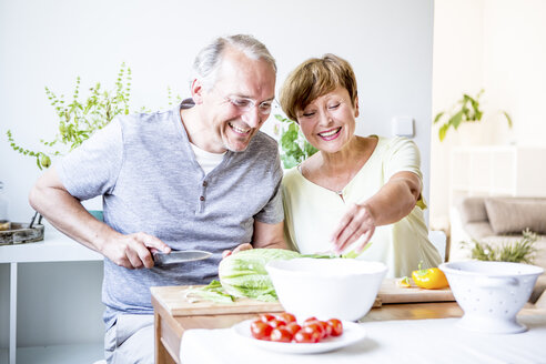 Happy senior couple in kitchen preparing salad together - WESTF22755
