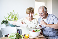 Happy senior couple in kitchen preparing salad together - WESTF22758