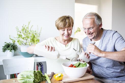 Happy senior couple in kitchen preparing salad together - WESTF22758