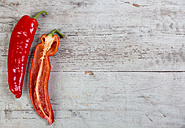 Whole and half red pointed pepper on wood - JUNF00837