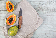 Whole and sliced papaya and a kitchen knife on paper and wood - JUNF00840