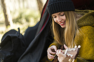 Smiling young woman playing guitar in tent - KKAF00411