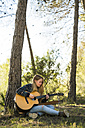 Young woman playing guitar in nature - KKAF00414