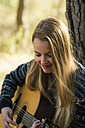 Smiling young woman playing guitar in nature - KKAF00417
