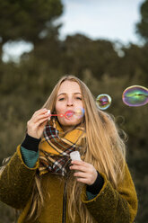 Portrait of young woman blowing soap bubbles in nature - KKAF00429